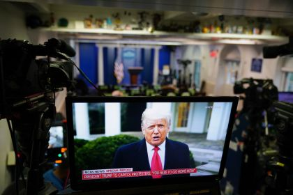 US President Donald Trump is seen on TV from a video message released on Twitter, seen in an empty Brady Briefing Room at the White House in Washington, DC on January 6, 2020. - Thousands of Trump supporters, fueled by his spurious claims of voter fraud, flooded the nation